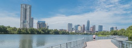 Panoramic view people enjoy outdoor activities on boardwalk in d. Panorama view people biking running walking along boardwalk near downtown Austin, Texas in royalty free stock image