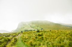 Panoramic view at the Pichincha volcano, with some native andes plants and tourist, with a typical hut in the horizont Royalty Free Stock Image