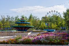Panoramic View on the Play and rest zone in the city park, called Kio. Large Fountain, Wheel, Flags, Flowers and Playground. stock photos