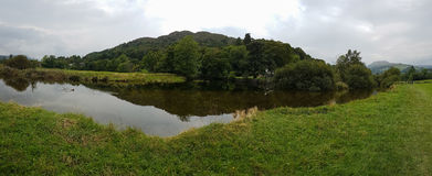 Panoramic view of pond in Ambleside countryside, Cumbria, UK. Panoramic view of pond and beautiful reflections in Ambleside countryside, Cumbria, UK Royalty Free Stock Images