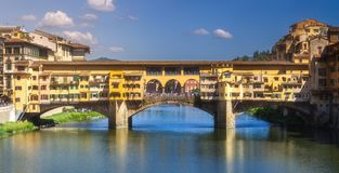 Panoramic view of Ponte Vecchio Bridge, Florence. Panoramic view of Ponte Vecchio Bridge with reflection on river during sunny day, Florence, Italy stock photos