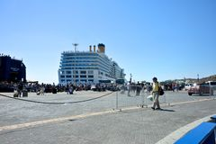 View of port with Costa Deliziosa cruise ship moored in the new port of Mykonos and people ready to embark. Panoramic view of port with Costa Deliziosa cruise stock image