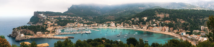 Panoramic view of Port de Soller, Mallorca. Panoramic view of Port de Soller with harbour, yachts, tourist boats, colorful architecture and beach on a cloudy day Stock Images