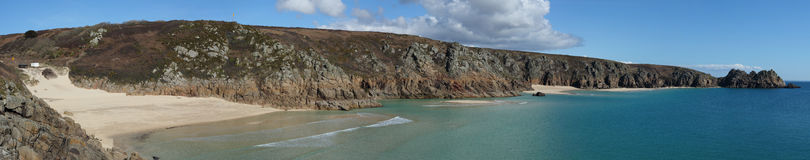 Panoramic view Porthcurno beach to Logan rock. Royalty Free Stock Photos