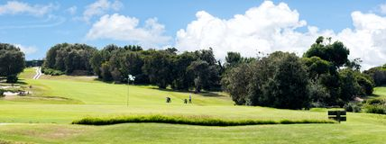 A panoramic view of golf course fairway and putting green. A panoramic view of putting green and large fairway with rich solid clouds in the background stock images