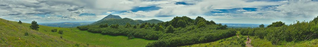 Panoramic shot of puy de dome. Panoramic view of the puy de dome with clouds and walkers Royalty Free Stock Photo