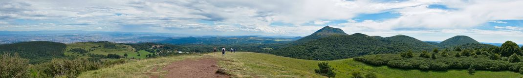 Panoramic shot of puy de dome. Panoramic view of the puy de dome with clouds and walkers Stock Photo