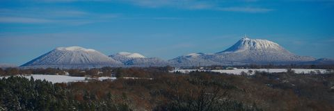 Panoramic view of the puy de dome and the puy de come under the snow. Blue sky and forest Royalty Free Stock Photo