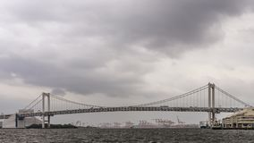 Panoramic view of the Rainbow Bridge in Tokyo, Japan, on a rainy day with cloudy sky stock photos