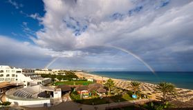 Panoramic view of rainbow over sea and beach royalty free stock images
