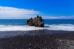 Panoramic view at the rock formation on a beach against blue sky. Praia Formosa beach in Funchal on Portuguese island of Madeira royalty free stock photos