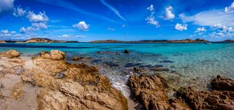 Panoramic view of a rocky beach with clear colorful water stock images