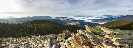 Panoramic view from rocky mountains into valleys with low clouds Royalty Free Stock Images