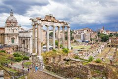 Roman Forum, Rome`s historic center, Italy. Panoramic view of Roman Forum with ancient ruins of temple, columns of Saturn, Triumphal Arch of Septimius Severus Stock Photos
