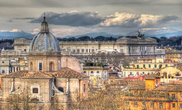 Panoramic view of Rome. Panoramic view of Rome on the background of clouds and mountains. In the foreground the church Santa Maria in Campitelli. In the Royalty Free Stock Photo