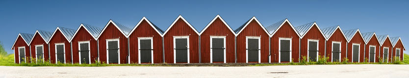 Panoramic view of row of red wooden boathouses Royalty Free Stock Images