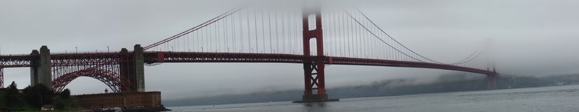 Panorama San Francisco Golden Gate Bridge disappearing in the fog royalty free stock image