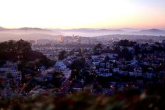 Panoramic View of San Francisco from Twin Peaks at Sunset. City view at dusk, with lights and the Golden Gate Bridge hiding in the fog Royalty Free Stock Image