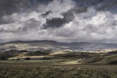 Panoramic view on scenic mountain valley in Lake District,Cumbria,Uk. Low clouds rolling over mountain peaks and sunlight patches on hills.Panoramic view on royalty free stock photography