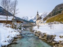 Panoramic view of scenic winter landscape in the Bavarian Alps with famous Parish Church of St. Sebastian in the village of Ramsau Stock Photography