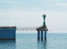 Panoramic view of sea pier with lighthouse tower. Panoramic view of of sea pier with lighthouse tower. Nautical landscape stock photo