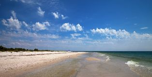 Panoramic view on sea with sand beach and blue sky with clouds. At sun summer day Stock Images
