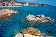 Panoramic view of seashore with rock cliff and a town on background. In Lloret de Mar, Catalonia, Costa Brava, Spain Royalty Free Stock Image