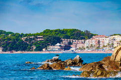 Panoramic view of seashore with rock cliff and a town on background. In Lloret de Mar, Catalonia, Costa Brava, Spain Royalty Free Stock Photos