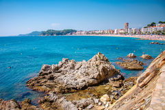Panoramic view of seashore with rock cliff and a town on background. In Lloret de Mar, Catalonia, Costa Brava, Spain Royalty Free Stock Images