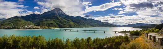 Serre-Poncon Lake with Savines-le-Lac and the Grand Morgon mountain peak in Summer. Alps, France. Panoramic view of Serre-Poncon Lake with Savines-le-Lac and its Royalty Free Stock Image