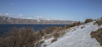 Panoramic view of Sevan Lake with snow maintains around of it Royalty Free Stock Photo