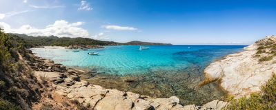 Boats in a small rocky cove with sandy beach in Corsica Stock Images