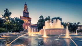 Panoramic view of Sforza Castle in Milan. Panoramic view of Sforza Castle Castello Sforzesco with lighting fountain at night, Milan, Italy. This castle was built stock images