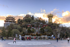 Panoramic view of Shangri-La Golden Temple at sunset with some tourists walking by Stock Photography