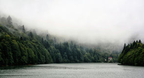Panoramic view of Shaori lake at rainy day. RACHA - GEORGIA - SEPTEMBER 2016: Panoramic view of Shaori lake at rainy day. Near the water a house with red roof Stock Photos