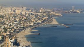 Panoramic view of Sharjah coastline from Ajman rooftop timelapse - third largest and most populous city in United Arab Emirates. Sharjah is located along royalty free stock photography