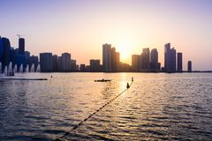 Panoramic view of Sharjah waterfront in UAE at sunset. Panoramic sunset view of Sharjah waterfront cityscape in UAE Stock Photography