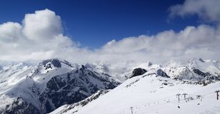 Panoramic view on ski slope and cloudy mountains at nice sun day Royalty Free Stock Photos