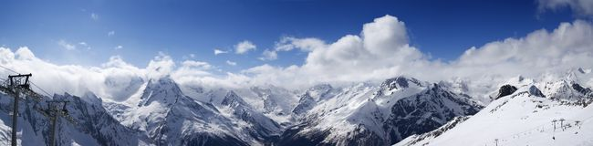 Panoramic view on ski slope and cloudy mountains at sun day Stock Photo