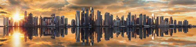 Panoramic view of the skyline of Doha, Qatar, at sunset time. Panoramic view of the modern skyline of Doha, Qatar, at sunset time with reflection in the water stock image