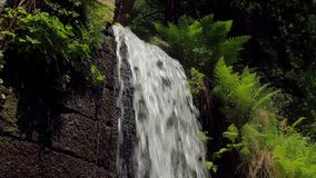 Panoramic view of small artificial waterfall in sunny spring day stock footage