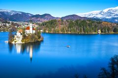 Panoramic view of small natural island in the middle of alpine lake with church dedicated to assumption of Mary and castle stock photos