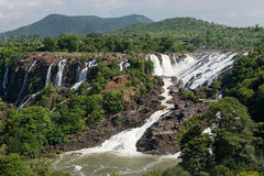 Panoramic view of small waterfall falling side by side with hill in background Royalty Free Stock Photos