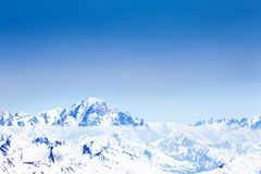 Panoramic view of snow caped Mont Blanc mountain. Panoramic view of snow caped Alpine Mont Blanc mountains in clouds stock photo