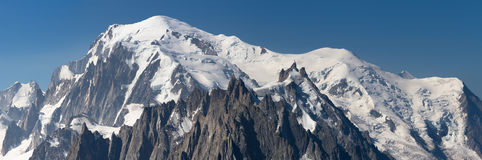 Panoramic view on snow covered mountains. Panoramic view on the Mont Blanc in the alps standing out over the Aiguille du Midi mountain range Royalty Free Stock Images