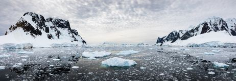 Panoramic view of snow covered mountains and water with ice, Lemaire Channel, Antarctica. Panoramic view of snow covered mountains and water filled with ice stock photography