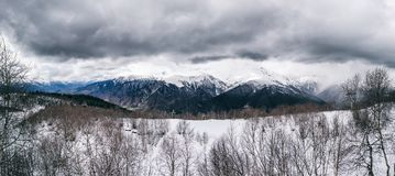 Panoramic view on snow winter mountains and cloud sky. Caucasus Mountains. Svaneti region of Georgia. Dramatic Panoramic view on snow winter mountains and Royalty Free Stock Image