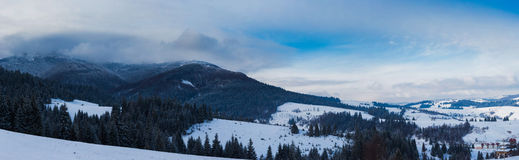 Panoramic view on snowy forest and little village. From top of hill Royalty Free Stock Photo