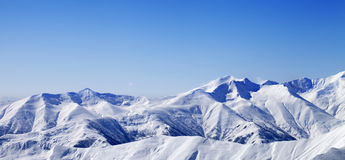 Panoramic view on snowy winter mountains and blue sky Royalty Free Stock Photography