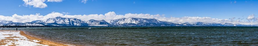 Panoramic view of south Lake Tahoe taken from a snow covered sandy beach, on a sunny day; snow covered mountains in the background. California stock photography